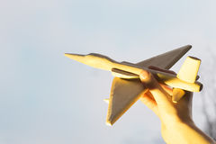 La mano con un aeroplano de madera en el fondo de la puesta del sol Aero- Alca L-159 Foto de archivo
