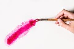 La mano con un cepillo dibuja la línea roja Fotos de archivo libres de regalías