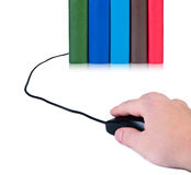 La mano con un ratón del ordenador conectó con los libros. Fotografía de archivo libre de regalías