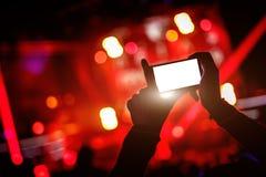 La mano con un smartphone registra el festival de música en directo, concierto vivo, demostración en etapa Foto de archivo libre de regalías