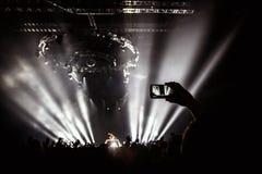 La mano con un smartphone registra el festival de música en directo, tomando la foto de la etapa del concierto Imagenes de archivo