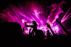 La mano con un smartphone registra el festival de música en directo, tomando la foto de la etapa del concierto Fotografía de archivo libre de regalías