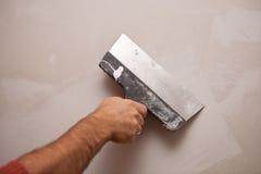 La mano con una spatola, lavoro allinea la parete Fotografia Stock Libera da Diritti