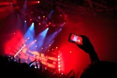La mano con uno smartphone registra il festival di musica in diretta, prendente la foto della fase di concerto Fotografia Stock Libera da Diritti
