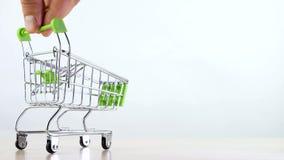 La mano controla el carro de la compra o la cesta de la compra isoleted en el fondo blanco metrajes