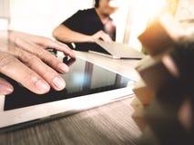 La mano creativa que trabaja la tableta digital y la madera desconciertan con el ordenador portátil Imagenes de archivo