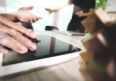 La mano creativa que trabaja la tableta digital y la madera desconciertan con el ordenador portátil Fotos de archivo libres de regalías