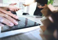 La mano creativa que trabaja la tableta digital y la madera desconciertan con el ordenador portátil Foto de archivo libre de regalías