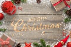 La mano creativa talló el texto de la Feliz Navidad en una superficie de madera Rodeado con las decoraciones de la Navidad Foto de archivo libre de regalías