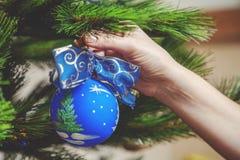 La mano cuelga en bola azul hermosa del árbol de navidad con el arco Imagenes de archivo