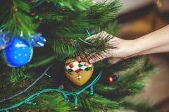 La mano cuelga en el juguete hermoso del árbol de navidad con el corazón Imagen de archivo