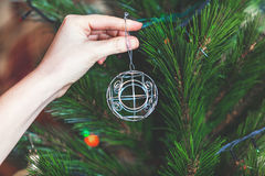 La mano cuelga en la bola elegante del árbol de navidad del alambre Imagenes de archivo