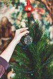 La mano cuelga en la bola elegante del árbol de navidad del alambre Fotos de archivo libres de regalías