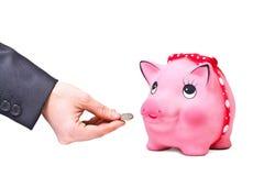 La mano dà la moneta a moneybox Fotografia Stock Libera da Diritti