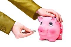 La mano dà la moneta a moneybox Immagini Stock