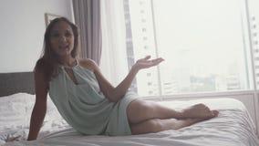La mano d'ondeggiamento della giovane donna castana felice su video chiacchierata si siede sul letto in appartamento Movimento le video d archivio