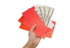 La mano da el billete de banco del efectivo del dólar del dinero en sobre rojo foto de archivo libre de regalías