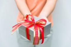 La mano da el rectángulo de regalo de plata con la cinta roja Imagen de archivo