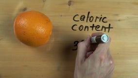 La mano de Dietologist anota el contenido calórico de la naranja en superficie de madera metrajes