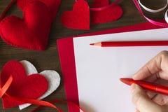 La mano de Emale escribe una nota el día del ` s de la tarjeta del día de San Valentín Imagen de archivo libre de regalías