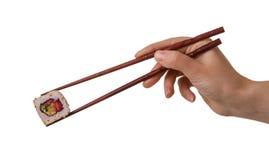 La mano de la hembra guarda los rollos de sushi con los palillos de madera aislados en blanco Foto de archivo libre de regalías