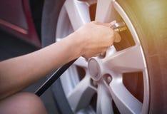 La mano de la hembra infla un neumático antes de viajar foto de archivo