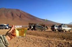 La mano de la hembra que sostiene una taza de té de la mañana en la frontera de Chile-Bolivia con muchos de las furgonetas del ca imagenes de archivo