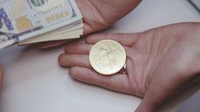 La mano de la hembra una lleva a cabo el bitcoin y otra toma dólares de la mano masculina almacen de metraje de vídeo