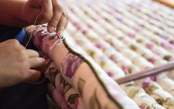 La mano de la costurera que cose el colchón Foto de archivo