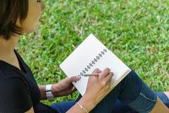 La mano de la muchacha asiática escribe una nota imágenes de archivo libres de regalías