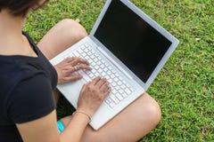 La mano de la muchacha asiática que mecanografía en el ordenador portátil Imagen de archivo