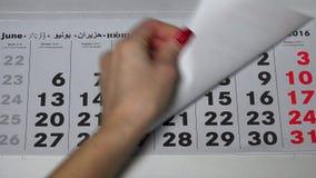 La mano de la muchacha con los clavos barnizados rasga apagado las páginas de papel del calendario más allá de 2016 años