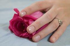 La mano de la muchacha en color de rosa se levantó Fotografía de archivo