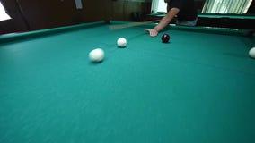 La mano de la muchacha pone la bola en la tabla de billar Bola de billar roja grande en el primero plano metrajes