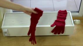 La mano de la muchacha puso guantes de lana rojos en el radiador en casa almacen de metraje de vídeo