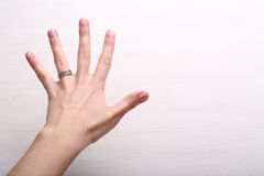 La mano de la mujer con el anillo en fondo ligero Imagenes de archivo