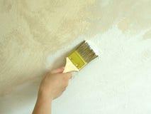 La mano de la mujer con la pared de la pintura del cepillo Imagen de archivo libre de regalías
