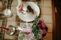La mano de la mujer con la torta en la tabla Fotos de archivo