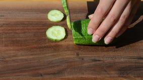 La mano de la mujer de la velocidad cortó el tablero de madera del cuchillo ecológico verde del pepino almacen de video