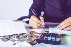 La mano de la mujer de negocios que calcula sus costos mensuales durante la estación del impuesto con las monedas, la calculadora fotos de archivo