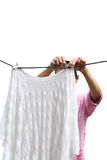 La mano de la mujer del quehacer doméstico que cuelga el lavadero mojado limpio para secar la ropa es Imagen de archivo