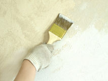 La mano de la mujer en guante con la pared de la pintura del cepillo Fotos de archivo libres de regalías