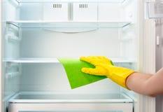 La mano de la mujer en refrigerador amarillo de la limpieza del guante con el trapo verde Foto de archivo libre de regalías