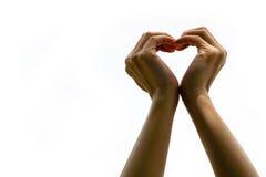 La mano de la mujer hace que un corazón forma el aislante, tarjeta del día de San Valentín Imagen de archivo