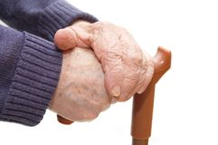 La mano de la mujer mayor se inclina en el bastón Imagenes de archivo