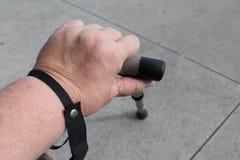 La mano de la mujer obesa que sostiene un bastón Fotos de archivo libres de regalías
