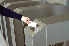 La mano de la mujer pone la tarjeta plástica blanca al primer del lector Imágenes de archivo libres de regalías