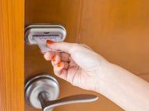La mano de la mujer que inserta la llave electrónica Fotografía de archivo