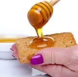 La mano de la mujer que lleva a cabo una tostada con la miel que fluye de un di de la miel Foto de archivo libre de regalías