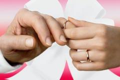 La mano de la mujer que pone en un anillo de bodas en el finger de un hombre Foto de archivo libre de regalías